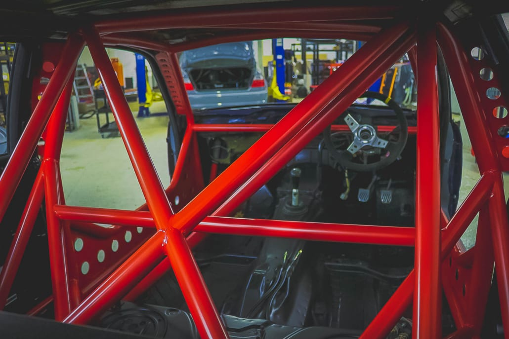 Red Sparco Roll Cage In A BMW E36 Track Car With A Stripped Interior